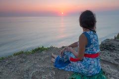 Mujer joven en la puesta del sol en el área de Uluwatu, Bali, Indonesia Imagen de archivo libre de regalías