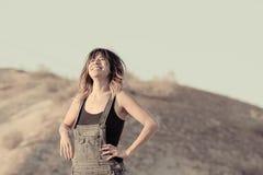 Mujer joven en la risa de los guardapolvos Imagen de archivo libre de regalías