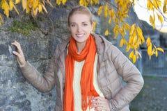 Mujer joven en la ropa caliente que presenta contra la pared de piedra Fotos de archivo