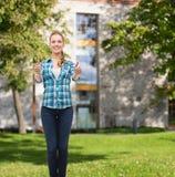 Mujer joven en la ropa casual que muestra los pulgares para arriba Fotografía de archivo libre de regalías