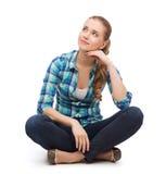 Mujer joven en la ropa casual que se sienta en piso Fotos de archivo