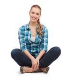 Mujer joven en la ropa casual que se sienta en piso Foto de archivo