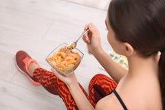 Mujer joven en la ropa de la aptitud que desayuna sano en casa fotografía de archivo libre de regalías