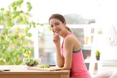 Mujer joven en la ropa de la aptitud que prepara el desayuno sano imagen de archivo