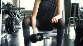 Mujer joven en la ropa de deportes que hace ejercicio asentado del bíceps del rizo de la concentración de la pesa de gimnasia en  almacen de metraje de vídeo