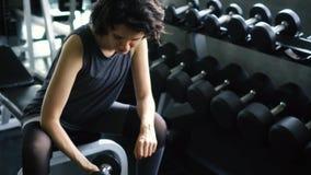Mujer joven en la ropa de deportes que hace ejercicio asentado del bíceps del rizo de la concentración de la pesa de gimnasia en  almacen de video