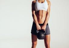 Mujer joven en la ropa de deportes que sostiene una campana de la caldera imagen de archivo