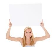Mujer joven en la ropa interior que lleva a cabo la muestra en blanco Fotografía de archivo libre de regalías