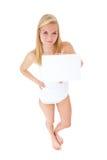 Mujer joven en la ropa interior que lleva a cabo la muestra en blanco Fotos de archivo