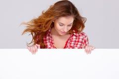 Mujer joven en la ropa ocasional que lleva a cabo a la tarjeta vacía Foto de archivo libre de regalías