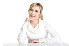 Mujer joven en la ropa ocasional que se sienta en el escritorio Fotografía de archivo