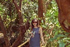 Mujer joven en la selva en el puente en planta tropical de la especia Fotos de archivo libres de regalías