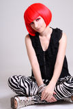 Mujer joven en la sentada roja de la peluca Foto de archivo libre de regalías