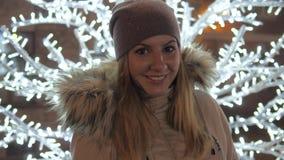 Mujer joven en la sonrisa caliente de la ropa, colocándose en medio de iluminaciones de la Navidad almacen de metraje de vídeo