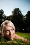 Mujer joven en la sonrisa de la hierba imagenes de archivo