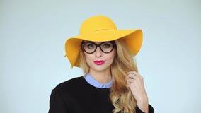 Mujer joven en la sonrisa de los vidrios En sombrero amarillo almacen de metraje de vídeo