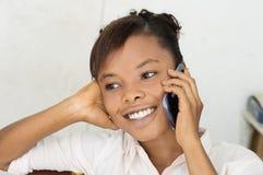 Mujer joven en la sonrisa del teléfono Imagen de archivo