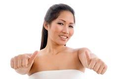 Mujer joven en la toalla que muestra el pulgar para arriba Fotografía de archivo