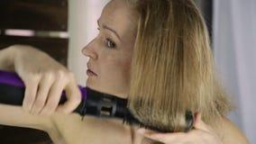 Mujer joven en la toalla que se peina el pelo con el peine caliente delante de un espejo Cuidado de piel y balneario casero almacen de metraje de vídeo