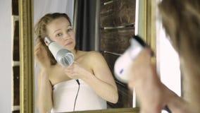 Mujer joven en la toalla que se seca el pelo delante de un espejo Cuidado de piel y balneario casero almacen de metraje de vídeo
