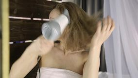 Mujer joven en la toalla que se seca el pelo delante de un espejo Cuidado de piel y balneario casero almacen de video