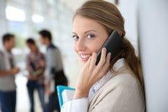 Mujer joven en la universidad que habla en el teléfono en vestíbulo Imágenes de archivo libres de regalías