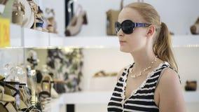 Mujer joven en la zapatería. almacen de video