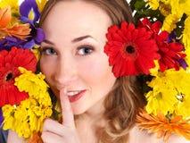 Mujer joven en las flores que hacen gesto del silencio. Fotos de archivo libres de regalías