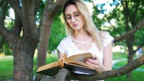Mujer joven en las lentes eaning en una rama de árbol y que leen un libro en el parque metrajes
