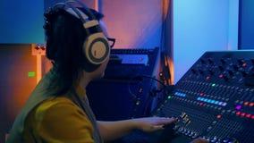 Mujer joven en las pistas de mezcla de mezcla de la consola al disco metrajes