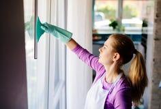 Mujer joven en las ventanas blancas de la limpieza del delantal fotos de archivo