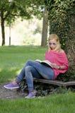Mujer joven en libro de lectura de los tejanos Fotos de archivo libres de regalías