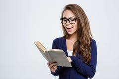 Mujer joven en libro de lectura de los vidrios Imagenes de archivo