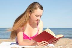 Mujer joven en libro de lectura rosado del bikini en la playa Imágenes de archivo libres de regalías