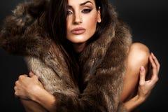 Mujer joven en lookin marrón del abrigo de pieles en la cámara fotografía de archivo