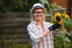 Mujer joven en los guantes de trabajo que toman el cuidado para la flor adentro en el jardín Imagenes de archivo