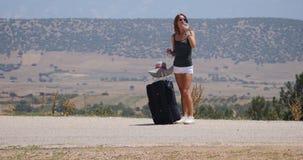 Mujer joven en los pantalones cortos blancos con equipaje almacen de metraje de vídeo