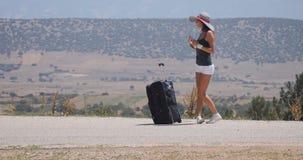 Mujer joven en los pantalones cortos blancos con equipaje almacen de video