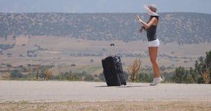 Mujer joven en los pantalones cortos blancos con equipaje metrajes