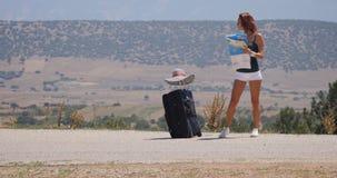 Mujer joven en los pantalones cortos blancos con equipaje y el mapa metrajes