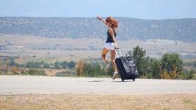 Mujer joven en los pantalones cortos blancos que corren feliz con la maleta metrajes