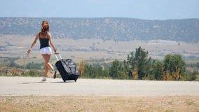 Mujer joven en los pantalones cortos blancos que corren feliz con la maleta almacen de metraje de vídeo