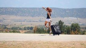 Mujer joven en los pantalones cortos blancos que corren feliz con la maleta almacen de video