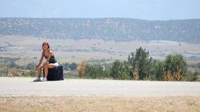 Mujer joven en los pantalones cortos blancos que se sientan en la maleta almacen de metraje de vídeo
