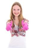 Mujer joven en los pulgares de goma rosados de los guantes para arriba aislados en blanco Imágenes de archivo libres de regalías