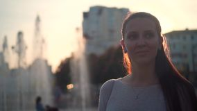 Mujer joven en los rayos de la puesta del sol en el fondo de la fuente y del paisaje urbano Espray y puesta del sol de agua de la almacen de video