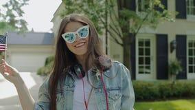 Mujer joven en los vidrios que agitan la bandera de las barras y estrellas delante de una casa de dos pisos en vecindad almacen de metraje de vídeo