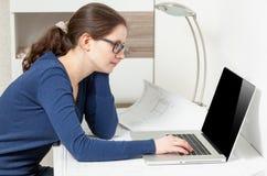 Mujer joven en los vidrios que se sientan detrás de la tabla y que miran el ordenador portátil Fotos de archivo libres de regalías