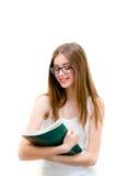 Mujer joven en los vidrios que sostienen el libro y que sonríen en el fondo blanco del copyspace Imagen de archivo libre de regalías