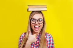 Mujer joven en los vidrios que sostienen los libros en su cabeza El estudiante elegante joven sonriente se está colocando con los Imagenes de archivo